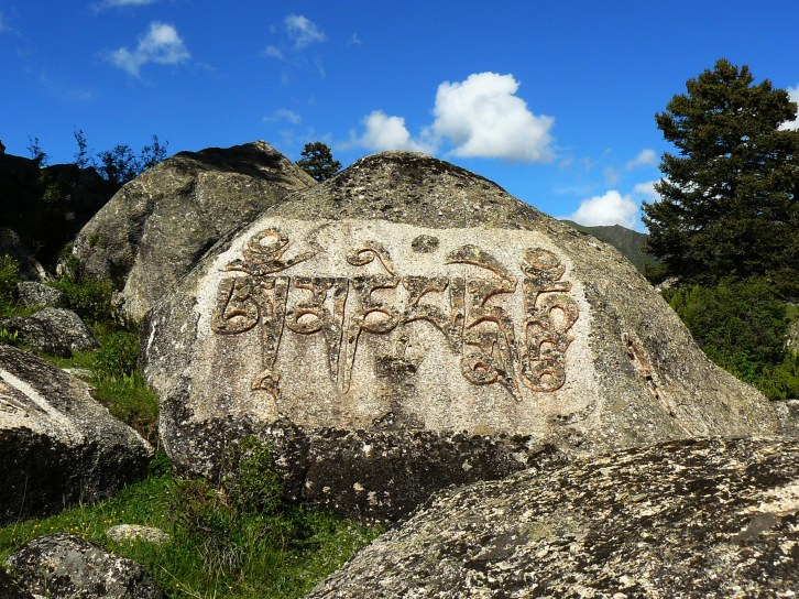 The Mani mantra on a boulder in Eastern Tibet.